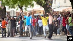 In this photo taken Monday, Oct. 26th, 2015 and made available Wednesday, Oct. 28th, 2015, youths supporting the opposition party dance and chant, predicting a win for their candidate, outside the Electoral Commission office in Stone Town, Zanzibar.