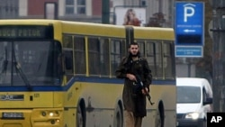 一个手持自动武器的枪手28日扫射美国使馆后走在萨拉热窝的街头