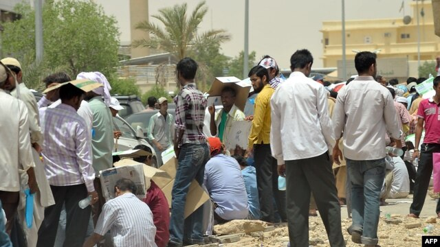 FILE - Foreign illegal laborers wait in a queue at the Saudi immigration offices at al-Isha quarter in al-Khazan district west of Riyadh, June 30, 2013.