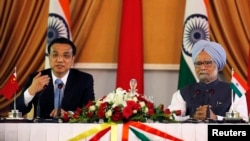 Chinese Premier Li Keqiang (L) speaks with the media as India's Prime Minister Manmohan Singh looks on during the signing of agreements ceremony in New Delhi, May 20, 2013.