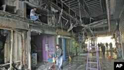 工人們2月13日晨開始清理雅典街頭在一夜暴力中被燒毀的店鋪門面