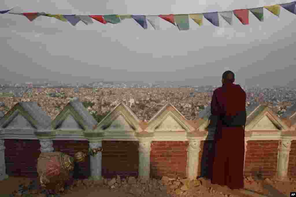 A Buddhist monk catches an aerial view of Kathmandu from the damaged Swayambhunath Stupa premises in Kathmandu, Nepal.