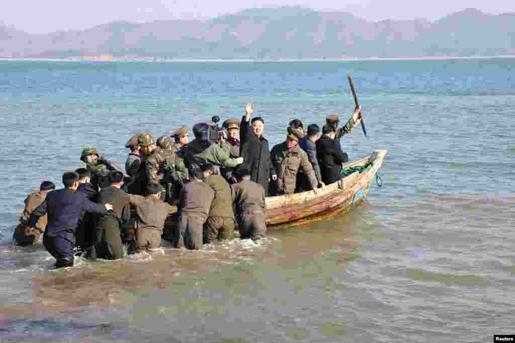 North Korean leader Kim Jong Un waves while in a boat during his visit to the Wolnae Islet Defence Detachment in the western sector of the front line, which is near Baengnyeong Island of South Korea March 11, 2013. (KCNA)