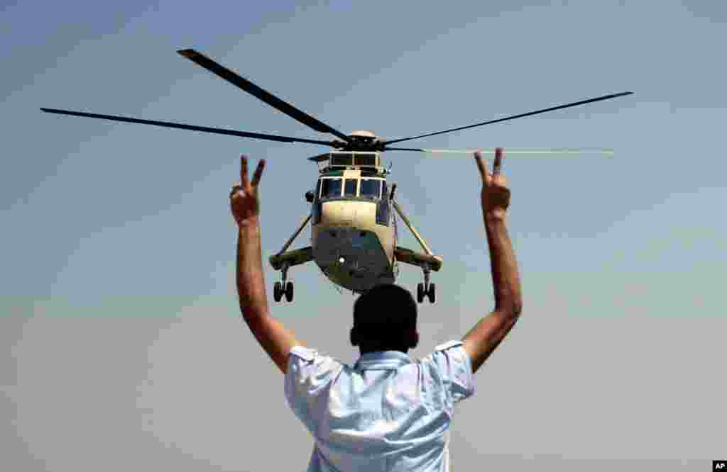A man flashes victory signs at a military helicopter near the presidential palace in Cairo, July 26, 2013.