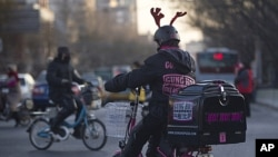 A pizza delivery man wearing a reindeer helmet rides an electric bicycle crossing a road junction in Beijing, China. Chinese leaders pledged fine-tuning to ensure stable and more balanced growth while fighting inflation, ending a top-level economic planni