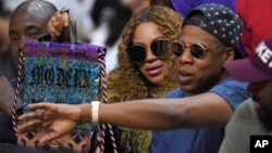 FILE - Beyonce and Jay Z watch during the first half in Game 7 of an NBA basketball first-round playoff series between the Los Angeles Clippers and the Utah Jazz, April 30, 2017, in Los Angeles.