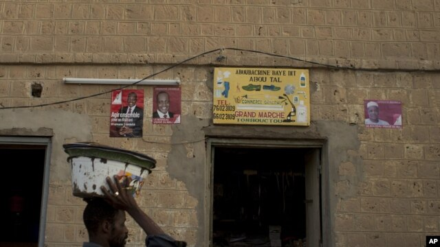 A vendor walks past a shop decorated with election posters supporting presidential candidate Dramane Dembele, in the central market area of Timbuktu, Mali, July 22, 2013.