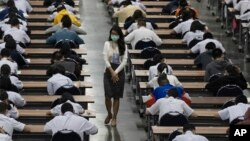 A teacher wears a protective mask as middle school students take an entrance examination for high school in Bangkok, Thailand, Thursday, March 5, 2020.