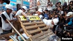 Para pekerja menghancurkan barikade di sebuah perempatan di jalan utama pusat belanja Mongkok, Hong Kong (25/11).