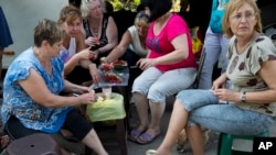 Women traveling from Moscow to their homes in Luhansk, Ukraine, eat a watermelon during a break in their bus journey at the Russia-Ukraine border control point in Donetsk, Rostov-on-Don region, Russia, Aug. 16, 2014.