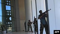 Lực lượng đối lập đụng độ với các chiến binh trung thành với ông Gadhafi bên ngoài khách sạn Corinthia ở Tripoli, nơi các nhà báo nước ngoài đang ở, ngày 25/8/2011