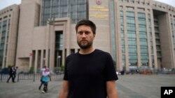 Andrew Gardner, seorang peneliti pada Amnesty International di Turki, berpose di luar gedung pengadilan di Istanbul (17/7), di mana 6 aktivis HAM akan diadili di sana.