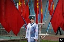 Nữ cảnh sát giao thông Bắc Triều Tiên đứng trước cờ Đảng trên đường phố Bình Nhưỡng, ngày 6/5/2016.