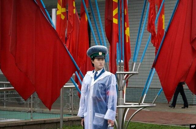 Nữ cảnh sát giao thông Bắc Triều Tiên trên đường phố được trang trí bằng cờ của Đảng Công nhân ngày 6/5/2016 ở Bình Nhưỡng.
