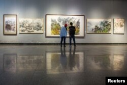 Visitors look at works by North Korean artists at the Mansudae Art Museum in the 798 art district in Beijing, China, September 20, 2017. (Reuters)