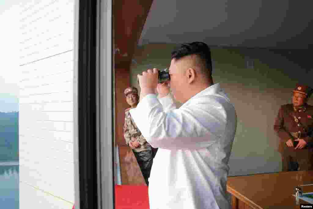 김정은 북한 국무위원장이 새로 개발한 정밀 조종유도체계를 도입한 탄도미사일 시험발사를 참관했다고 조선중앙통신이 30일 보도했다. 김 위원장이 망원경으로 미사일 시험발사 과정을 지켜보고 있다.