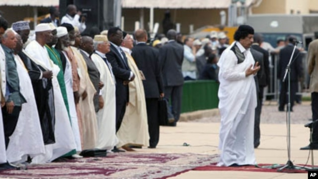 Libyan leader Moammar Gadhafi  (R) prays during the celebration of the birth of the Prophet in Uganda's capital, Kampala, on March, 19, 2008 along with the Ugandan president and other African leaders.