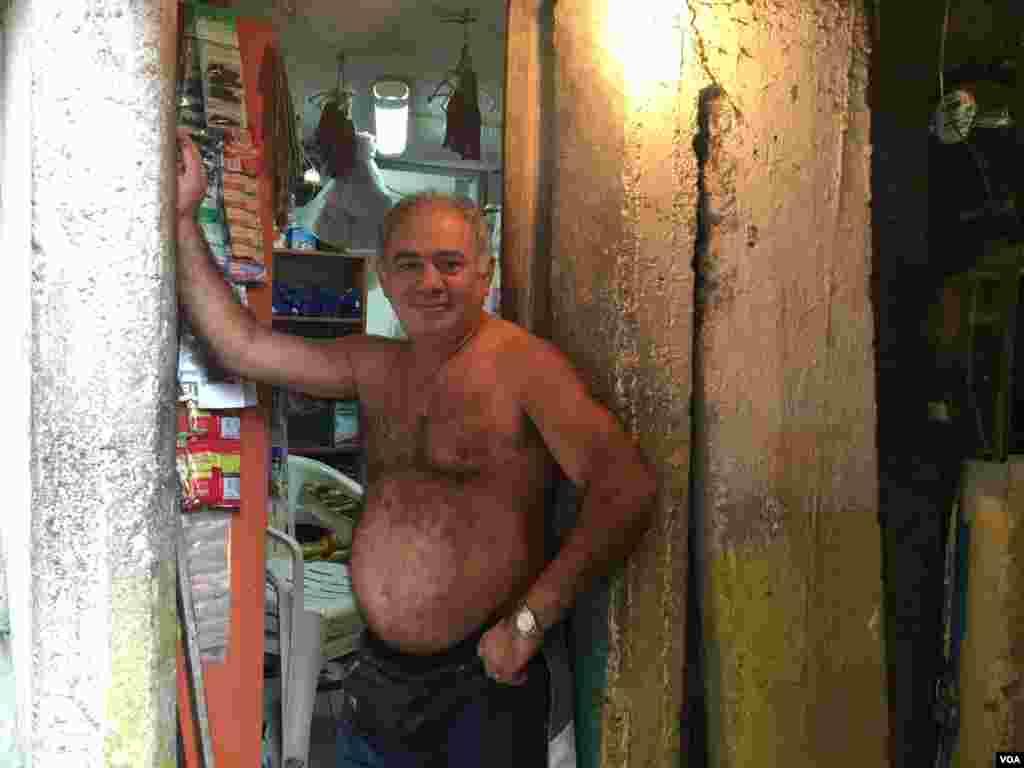 مغازه داری در منطقه ای زاغه نشین در ریو نزدیک ساحل لبنون. او هر طور که حس کند راحت تر است لباس می پوشد و گویا از پشه زیکا نمی ترسد.
