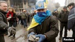 Người biểu tình chống chính phủ nhặt đá để chống trả với cảnh sát tại trung tâm thủ đô Kyiv, ngày 19/2/2014.