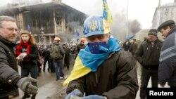 Manifestants anti-gouvernementaux rassemblant des pierres lors d'un rassemblement dans le centre de Kiev, 19 février 2014.