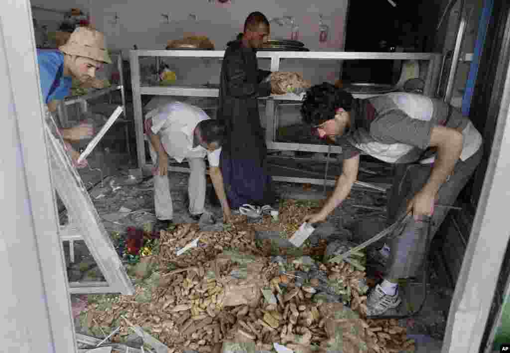 People clean up the aftermath of a car bomb attack at a bakery in the east Baghdad neighborhood of Kamaliya, Iraq, July 3, 2013.