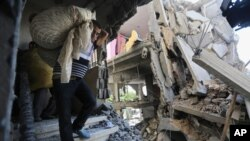 Palestinians carry belongings in a house after it was hit by an Israeli missile strike in Gaza City, July 11, 2014.