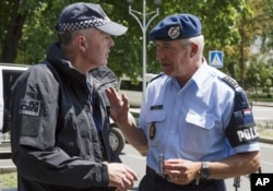 Dutch, right, and Australian policemen talk in the city of Donetsk, eastern Ukraine, July 27, 2014.