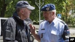 네덜란드(오른쪽)와 호주 경찰이 27일 우크라이나 도네츠크에서 대화를 하고 있다.