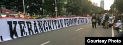 "Spanduk putih berukuran besar bertuliskan ""Pelantikan Anies-Sandi: Kebangkitan Pribumi Muslim""."