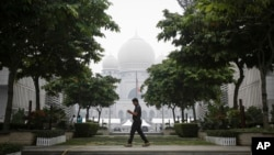 FILE - A Malaysian man walks past Palace of Justice shrouded in haze in Putrajaya, Malaysia, Sept. 11, 2015.