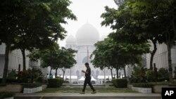 FILE - A Malaysian man walks past Palace of Justice shrouded in haze in Putrajaya, Malaysia, Sept. 11, 2015.
