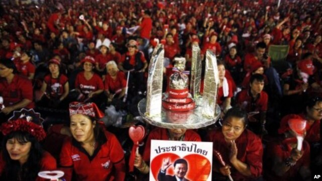 Anti-government ''red shirt'' protesters hold a picture of former Thai premier Thaksin Shinawatra as they wait for him to address them over a link during a rally near the Democracy monument, the site of bloody clashes with security forces last year, in Ba
