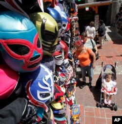 Masks hang over shoppers on Olvera Street during Cinco De Mayo festivities