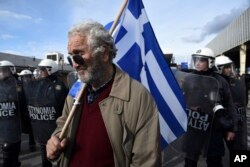 An opponent of Prespa Agreement holds a Greek flag in front of riot police during a protest in Evzones at the Greek-Macedonian border, Jan. 24, 2019.
