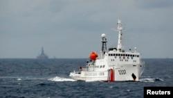Kapal penjaga pantai China siaga di dekat anjungan minyak China di laut China Selatan yang terlihat di latar belakang (foto: dok).