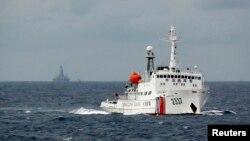 南中国海上的一艘中国海警船,不远处是中国的海上钻井平台。(2014年6月资料照)