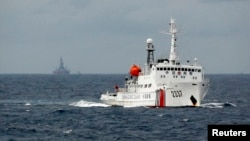 FILE - A Chinese Coast Guard vessel, with a disputed oil rig in the background, is seen in the South China Sea June 13, 2014.