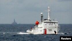 Tàu cảnh sát biển Trung Quốc phía trước giàn khoan dầu Hải Dương ở Biển Ðông, ngày 13/6/2014. Bộ Ngoại giao Trung Quốc xác nhận giàn khoan Hải Dương 981 ngày 15/7 đã hoàn tất công tác thăm dò ngoài khơi quần đảo Hoàng Sa 'đúng kế hoạch.'