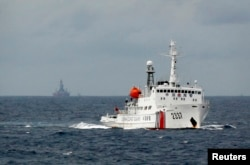 FILE - A Chinese Coast Guard vessel, with the disputed oil rig in the background, is seen in the South China Sea, June 13, 2014.