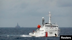 A Chinese Coast Guard vessel, with the disputed oil rig in the background, is seen in the South China Sea, June 13, 2014.