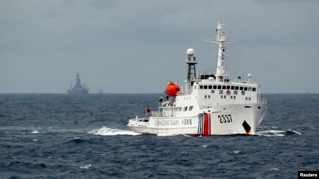 FILE - A Chinese Coast Guard vessel, with the disputed oil rig in the background, is seen in the South China Sea, June 2014.