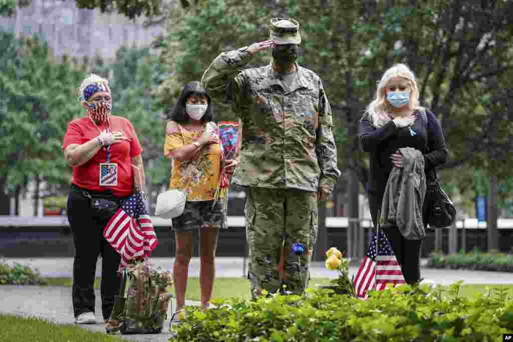 U.S. Army Sgt. Edwin Morales, center right, salutes after placing flowers for fallen FDNY firefighter Ruben D. Correa at the National September 11 Memorial and Museum in New York.