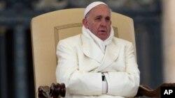 El papa Francisco intenta mantenerse caliente durante una audiencia general en la plaza de San Pedro.