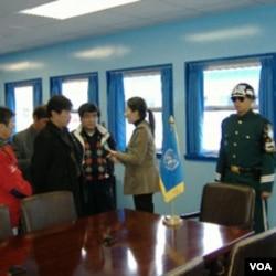 游客在非军事区停战谈判会议室内听导游讲解(美国之音王南拍摄)