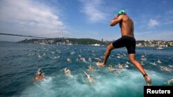 A competitor jumps into the water to swim from Asia to Europe during the annual Bosphorus Cross-Continental swimming competition in Istanbul ,July 7, 2013.
