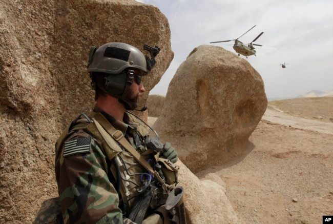 FILE - A U.S. special forces soldier takes cover as two Chinook Ch-47 helicopters come in for a landing with supplies in Afghanistan, Sept. 16, 2009.