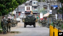 Philippine marines walk to the frontline in the continuing assaults to retake control of some areas of Marawi city, May 28, 2017, in southern Philippines