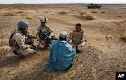 Sersan Marinir Amerika Serikat. Isaac Tate (kiri) dan Kpl. Aleksander Aleksandrov (tengah), mewawancarai seorang pria Afghanistan setempat dengan bantuan seorang penerjemah dari MEB, 11 Desember 2009. (AP)