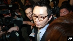 South Korean President Park Geun-hye's spokesman Yoon Chang-jung surrounded by journalists leaves after a press conference in Seoul, South Korea, May 11, 2013.