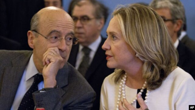 Secretary of State Hillary Rodham Clinton talks with France's Foreign Minister Alain Juppe during a meeting on Syria, April 19, 2012, in Paris
